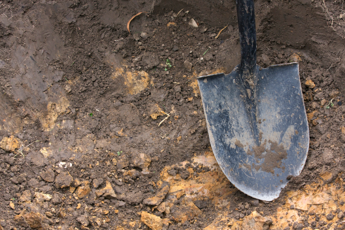 Close-up of spade shovel being used to dig a hole in soil