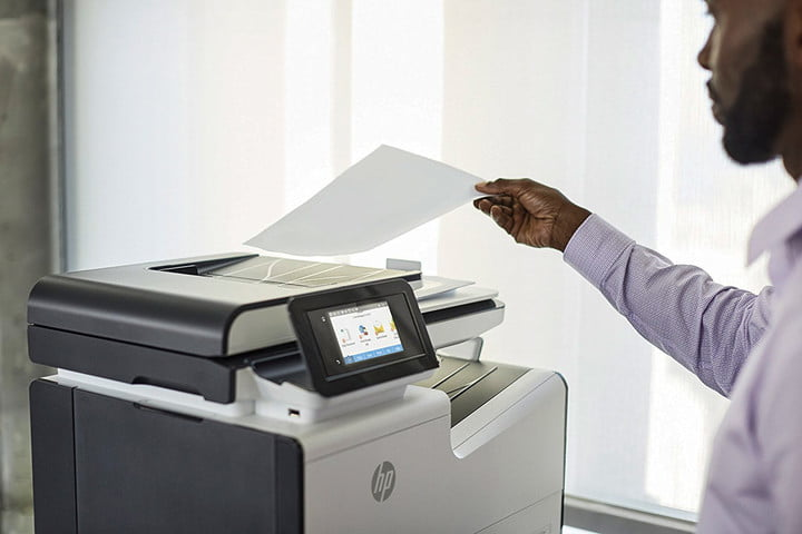 A person feeding a sheet of paper into a HP PageWide Pro 577dw printer.