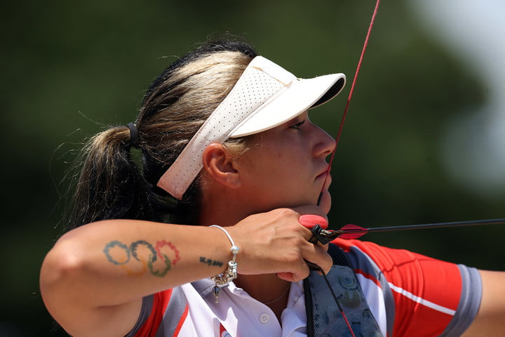 A female archer sporting a tattoo of the Olympic Rings pulls back the string of a bow with a nocked arrow.