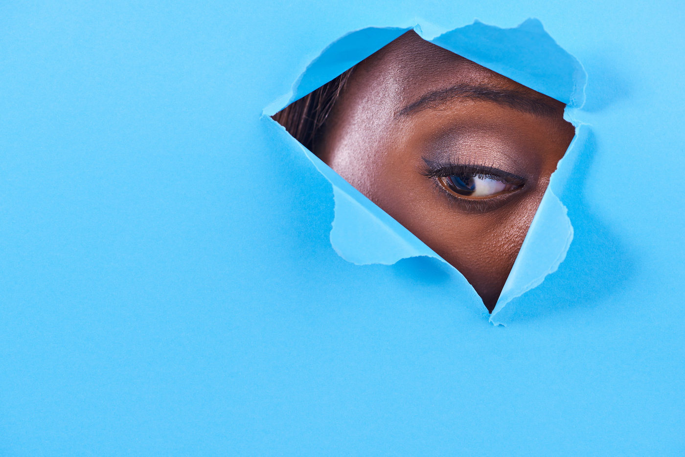 A view of a woman's eye looking through a hole in some colorful paper