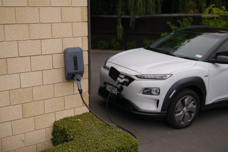 An electric vehicle charges along a house