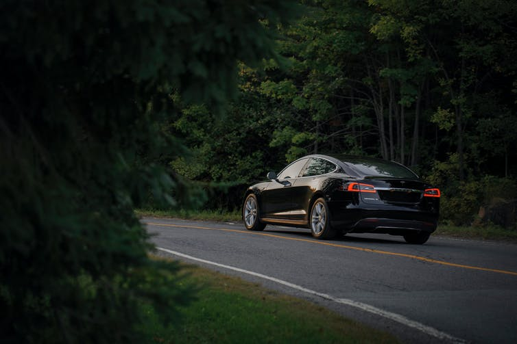 An electric vehicle drives through the forest